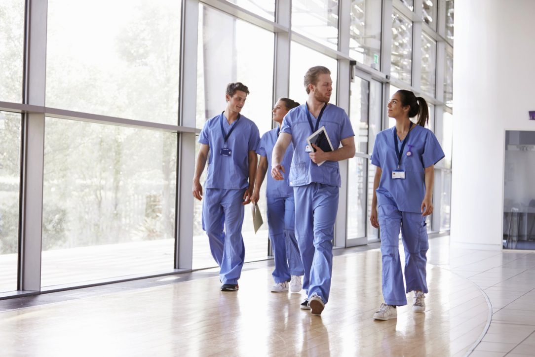 Healthcare workers walk through a hallway in a hospital
