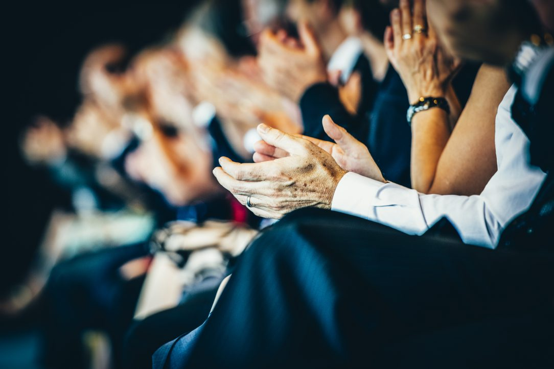 An audience clapping after listenging