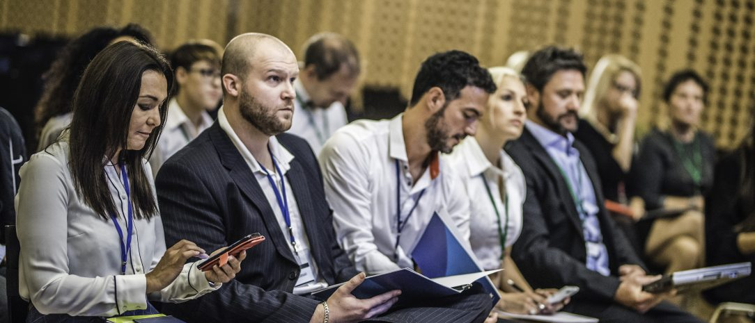People listening and taking notes during a conference